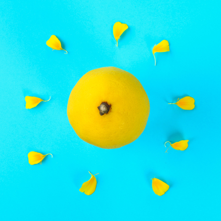 Yellow whole lemon in the form of the sun and rays from the petals of a yellow flower on a pastel blue background