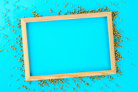 A wooden empty frame on a pastel background surrounded by shiny decorative stars and balls