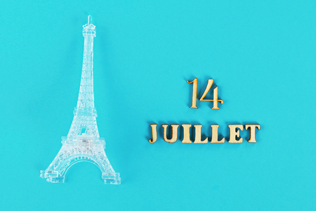 Text in French Good July 14. Miniature of the Eiffel Tower on a blue background. The concept of the holiday The day of the capture of the Bastille