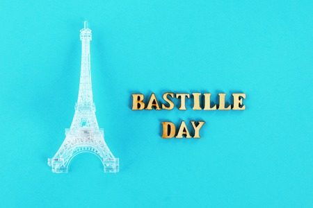 Miniature of the Eiffel Tower on a blue background. The concept of the holiday is July 14, the Day of the Bastille