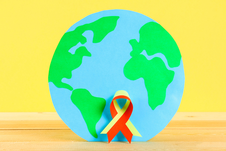 World Hepatitis Day. June 28th. Red yellow ribbon and planet earth on a wooden table against a yellow wall background