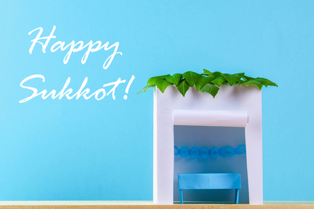 Text of Happy Sukkot. A hut made of paper covered with leaves on a blue background. Postcard, congratulations