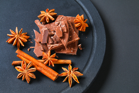 Pieces of chocolate, cinnamon and star anise on a dark grey table