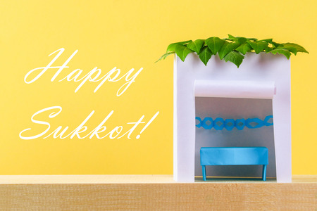 Text of Happy Sukkot. A hut made of paper covered with leaves on a yellow background. Postcard, congratulations