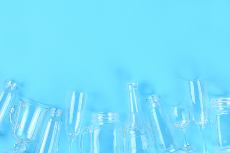 Glassware, glasses, jars on a pastel blue background. Flat lay, top view