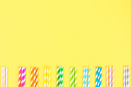 Multi-colored straw paper tubes on a bright yellow pastel background. Top view, copy space