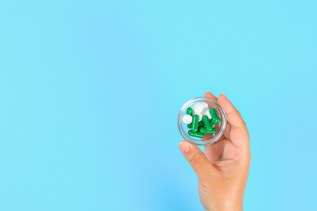 The girl holds in her hands blisters of various tablets and pills on the background of a blue table. Top view, copy space, flat lay Stock Photo