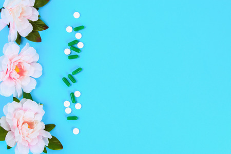 Capsules, pills and tablets with flowers on a blue table background. Top view, copy space, flat lay