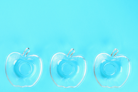 Glass cups for honey in the form of apples on a pastel of blue background. Rosh Hashanah