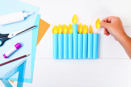 DIY. Eine Papiermenora mit eigenen Händen aus Papier. Menora für den jüdischen Feiertag Chanukka. Handgemacht für das Kind
