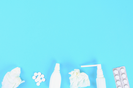 Medicines for flu, illness, cold, cough against a blue table with tablets. Top view, copy space, flat lay
