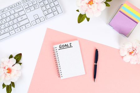 Write a goal for the new year 2010 in a white notebook on a white desktop next to a coffee mug and a keyboard. Top view, flat layout