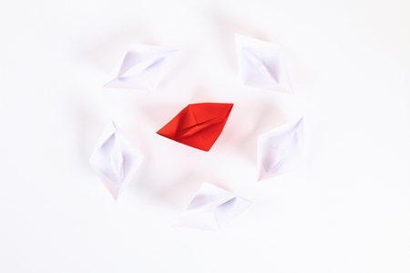 Red paper boat among other white. Leadership, white crow, individuality. Piranhas and a shark. Not like everyone else. Origami. Top view, flat lay, copy space Stock Photo
