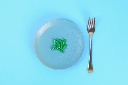 Eating pills as a regular meal. Pills on a plate on a blue table background. Top view, copy space, flat lay