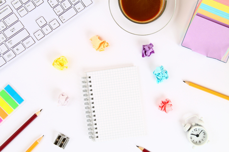 Crumpled multicolored sheets of paper on a white desktop next to a coffee mug and a keyboard. Top view, flat layout. Copy the space