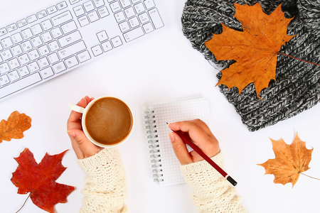 Coffee with marshmallow in hands on a white desktop next to an empty block and keyboard, autumn leaves. Fall mood. Top view, flat layout. Copy the space Stock Photo