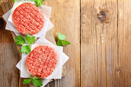 Raw minced meat for home made grill burgers cooking with spaces and herbs