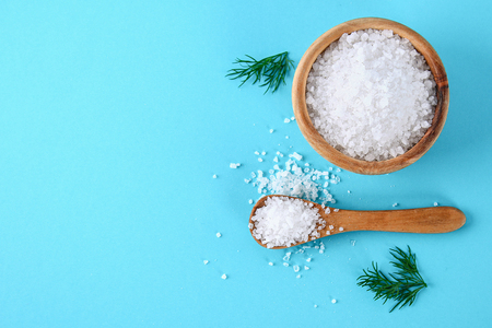 Crystals of large sea salt in a wooden bowl and spoon and dill on a blue table. Background for advertising salt. Table salty. Salted food