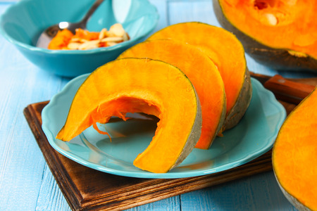 Sliced pumpkin into pieces for cooking pumpkin soup or mashed potatoes. Pumpkin on a blue wooden table