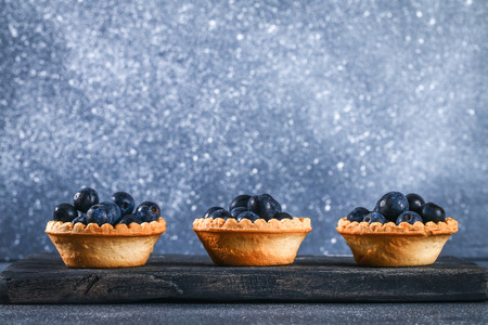 Blue blackthorn berries in sand tartlets on a table