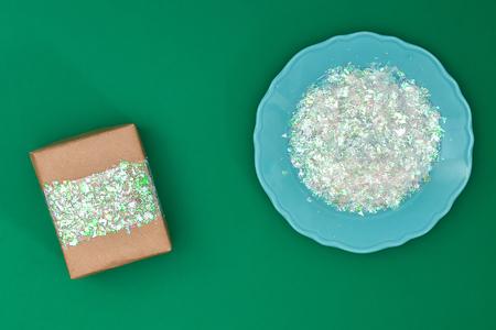 La conception originale d'un cadeau de Noël en papier kraft et en plastique brillant découpé, cellophane sur fond vert. Pas à pas sur la photo. Travail manuel, Bricolage Banque d'images