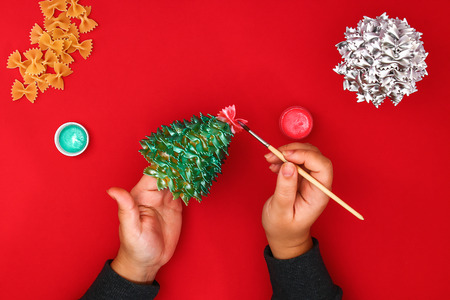 How to make a Christmas tree from raw pasta bows. The process of making Christmas trees from pasta, cardboard plates, hot glue and paint or spray. Guide, step by step on the photo. Handmade, DIY Stock Photo
