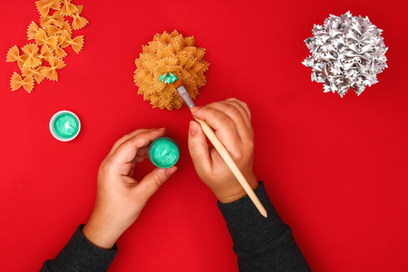 How to make a Christmas tree from raw pasta bows. The process of making Christmas trees from pasta, cardboard plates, hot glue and paint or spray. Guide, step by step on the photo. Handmade, DIY