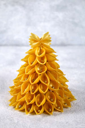 How to make a Christmas tree from raw pasta conchiglie. The process of making Christmas trees from pasta, cardboard plates, hot glue and paint or spray. Guide, step by step on the photo. Handmade, DIY Archivio Fotografico