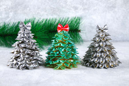 How to make a Christmas tree from raw pasta conchiglie. The process of making Christmas trees from pasta, cardboard plates, hot glue and paint or spray. Guide, step by step on the photo. Handmade, DIY Stock Photo