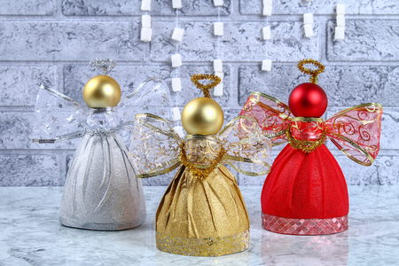 Diy Angel plastic bottle. Guide on the photo how to make a decorative angel from a bottle, self-adhesive shiny paper, ribbon and a Christmas ball with your own hands. Handmade. Step by step Stock Photo - 113199305