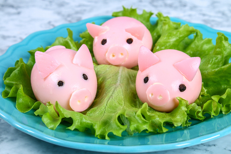 Diy pig from eggs. Workshop how to make a pig from a boiled egg painted in broth beets stuffed with stuffing. Appetizer on Christmas or New Year table. Top view. Creative decorative food for kid. Pig.