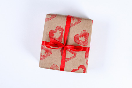 Diy. Gift wrapping for Valentine's Day. Kraft paper gift and potato stamp in the shape heart and red paint do it yourself on February 14th. Top view on a white background. step by step. Handicraft Banco de Imagens