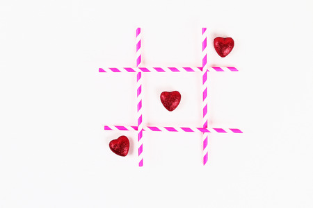 Valentine day layout. Noughts and crosses from pink straws and hearts on white background. Tic tac toe. St. Valentines Day, day love, February 14 concept. Copy space, top view, flat lay composition 写真素材