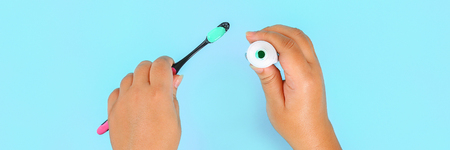 Banner. Woman squeezing toothpaste on brush against blue color background. Copy space. Top view