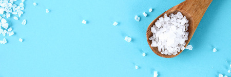 Crystals of large sea salt in a wooden spoon on a blue table Stockfoto