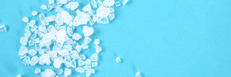 Crystals of large sea salt and dill on a blue table