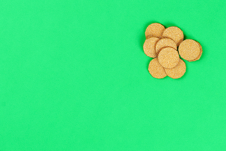 DIY Gold Coins of coins and shiny paper St Patricks Day on green background. Gift Idea, decor for leprechaun trap Saint Patricks Day. Step by step. Child kid craft process. Top view. Irish holiday.