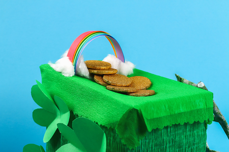 DIY leprechaun trap with gold coins, rainbow and green ladder St Patricks Day background. Gift Idea, decor Saint Patricks Day. Step by step. Child kid craft process. Top view. Irish holiday.