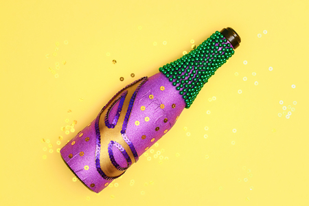 Diy Mardi Gras bottle purple self adhesive paper, green bead, carnival mask, sequins yellow background. Gift idea, decor Mardi Gras, Fat, Shrove Tuesday. Step by step. Top view. Process children craft