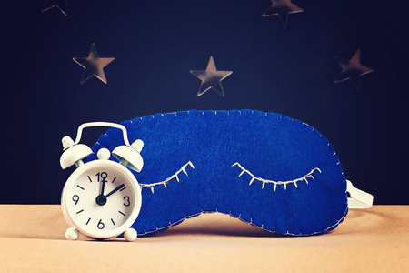 Sleeping mask handmade made of felt, stars on a black background. Kid craft. Children diy. White alarm clock showing midnight, 12 hours.