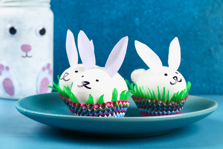 Diy rabbit from easter eggs on blue background. Gift ideas, decor Easter, spring. Handmade. White easter egg bunny, grass crepe paper, cup muffin cupcake. Step by step. Process kid crafts.