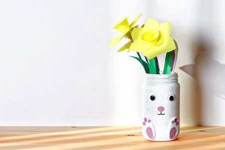 DIY Easter vase bunny with narcissus, daffodils from glass jar, felt, googly eyes on a white wall background. Gift ideas, decor for spring, Easter. Handmade. crafts. Kid Childrens Easter crafts. Archivio Fotografico - 117727083