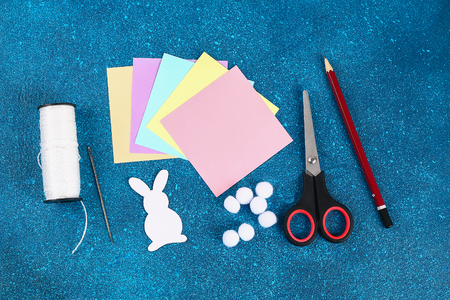 Diy Easter garland bunnies, flags with letters EASTER made of multicolor paper on a blue background. Gift idea, decor Spring, Easter. Step by step. Top view. Process kid children craft. Handmade.