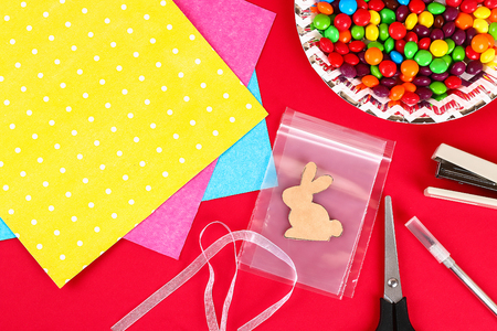 Diy Easter wrapping package sweets in a bag with a cut out bunny silhouette on a red background. Gift idea, decor Spring, Easter. Step by step. Top view. Process kid children craft. Stock Photo