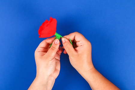 30 Diy paper red poppy Anzac Day, Remembrance, Remember, Memorial day made of crepe paper on blue background. Symbol war. Gift idea, decor. Step by step. Top view. Process kid children craft. Workshop