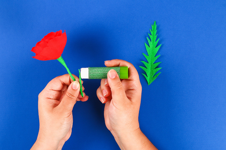 33 Diy paper red poppy Anzac Day, Remembrance, Remember, Memorial day made of crepe paper on blue background. Symbol war. Gift idea, decor. Step by step. Top view. Process kid children craft. Workshop