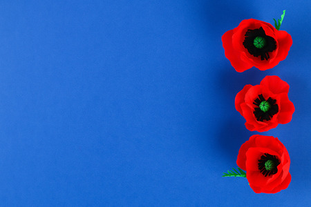 Diy paper red poppy Anzac Day, Remembrance, Remember, Memorial day made of crepe paper on blue background. Symbol war. Gift idea, decor. Step by step. Top view. Process kid children craft. Workshop