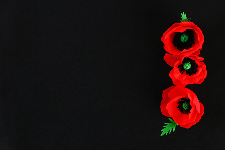 Diy paper red poppy Anzac Day, Remembrance, Remember, Memorial day made of crepe paper on black background. Symbol war. Gift idea, decor. Copy space. Top view. Banque d'images