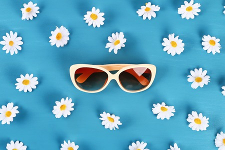Sunglasses and daisies on a blue background. Top view. Summer background. Flat lay. Standard-Bild