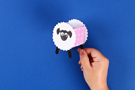 20 Diy Eid al adha lamb sheep sweet candy paper, wooden sticks for ice cream on blue background. Gift idea, decor Eid al adha. Step by step. Top view. Process kid children craft. Workshop.